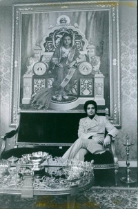 Prince Sayajirao Gaekwar sitting in front of a life-size portrait of his mother Sita Devi, Maharani of Baroda
